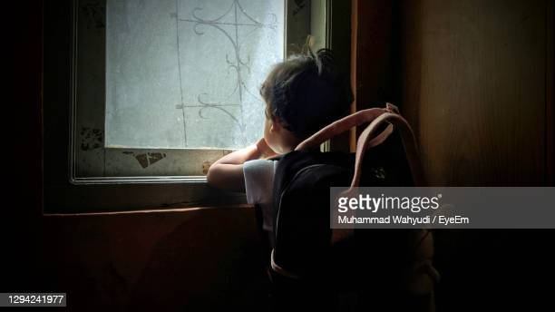 rear view of boy looking through window at home - homelessness stock pictures, royalty-free photos & images