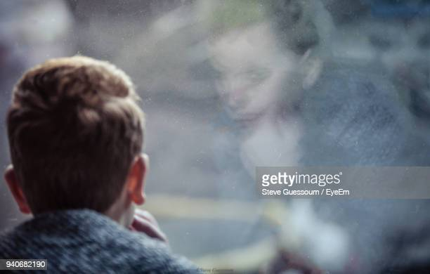 rear view of boy looking through window with reflection - steve guessoum stockfoto's en -beelden