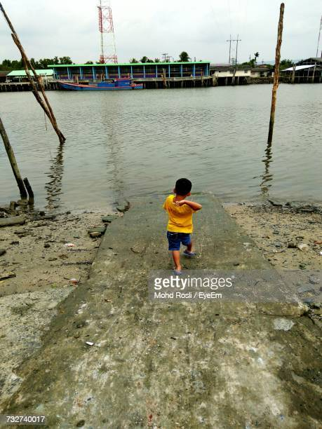 Rear View Of Boy On Riverbank Against Sky