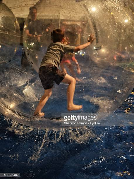 Rear View Of Boy On Zorb Ball Enjoying In Water At Gage County Fair