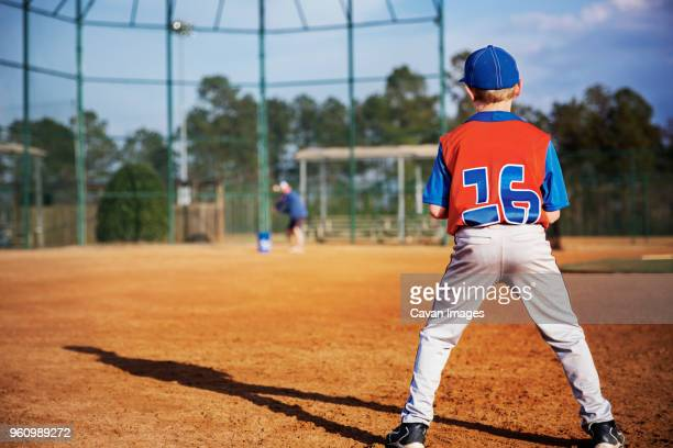 rear view of boy playing baseball on field - baseball uniform stock pictures, royalty-free photos & images
