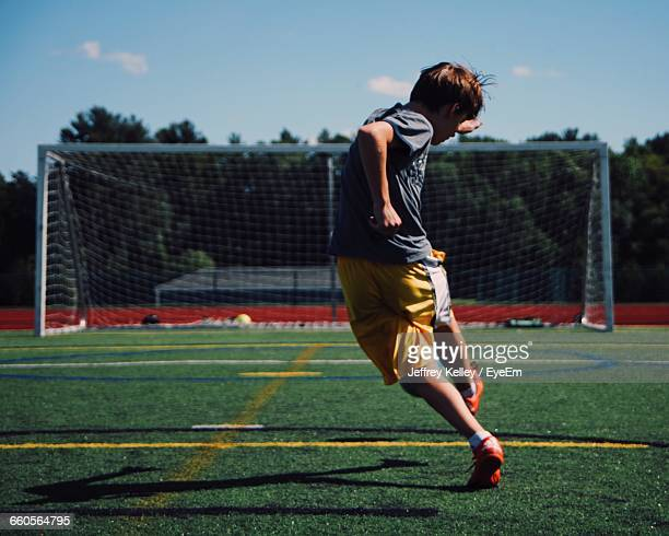 Rear View Of Boy Playing On Soccer Field