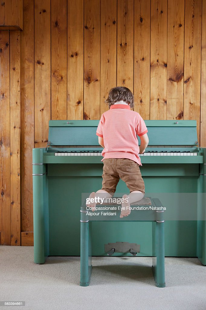 Rear view of boy playing piano : Stock Photo