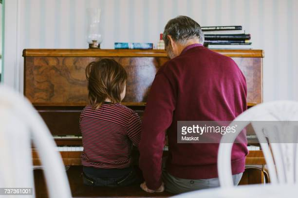 Rear view of boy playing piano with great grandfather at home
