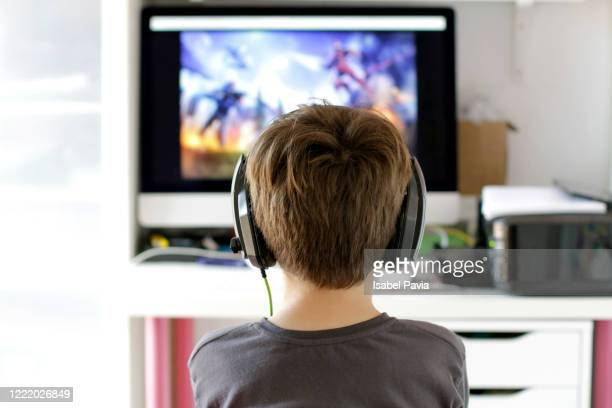 rear view of boy playing video game - leisure games stock pictures, royalty-free photos & images