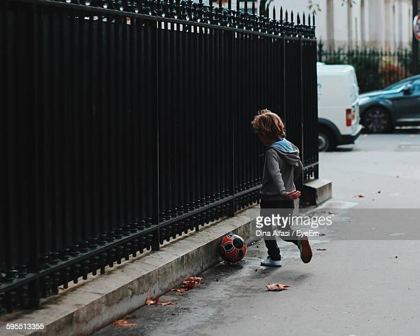 Rear View Of Boy Playing With Soccer On Street By Fence