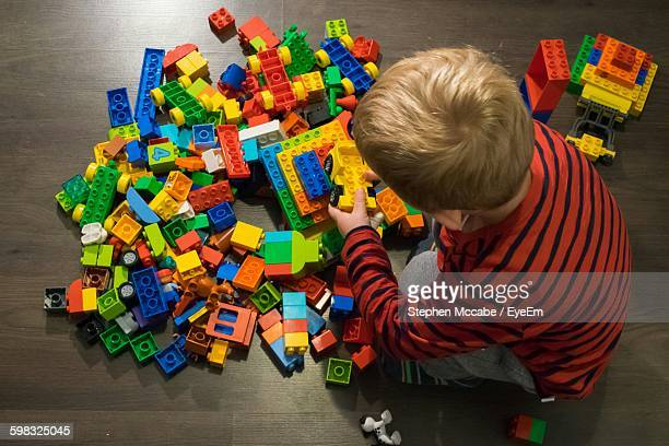 Rear View Of Boy Playing With Toy Blocks