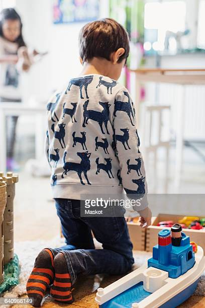 Rear view of boy playing with toys at preschool
