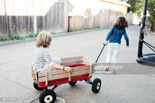rear view of boy pulling brother in toy wagon at yard - toy wagon stock photos and pictures