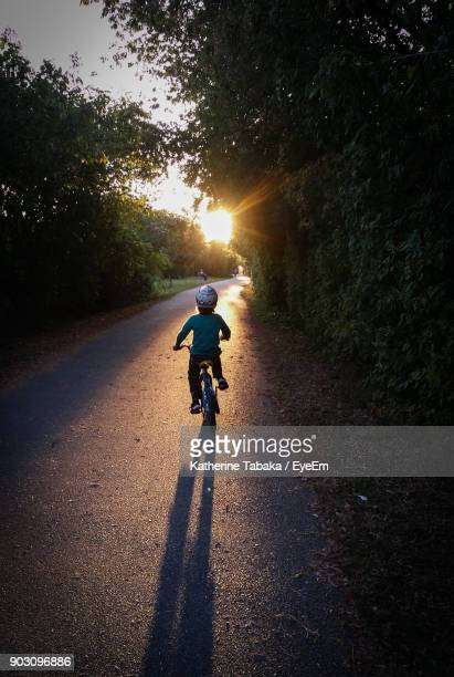 Rear View Of Boy Riding Bicycle On Street During Sunset