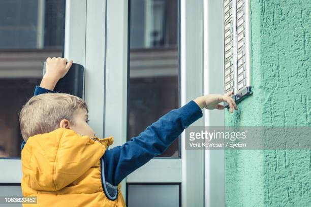 rear view of boy ringing doorbell - ringing doorbell stock pictures, royalty-free photos & images