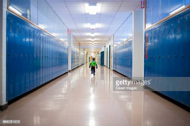 rear view of boy running in school corridor - corridor stock pictures, royalty-free photos & images