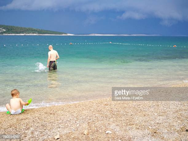 rear view of boy sitting at beach while father standing in sea against cloudy sky - sara mora fotografías e imágenes de stock