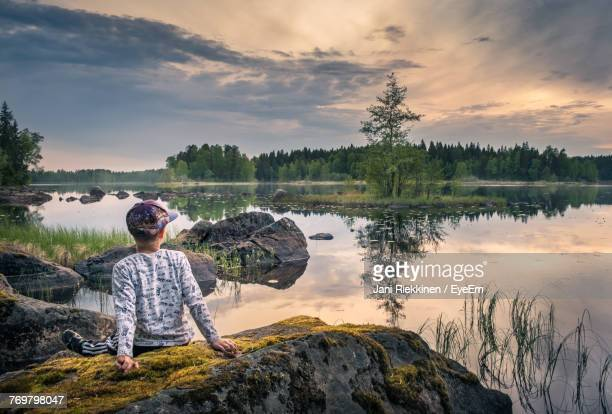 Rear View Of Boy Sitting By Lake Against Sky