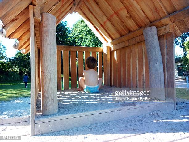 Rear View Of Boy Sitting In Wooden Hut At Park