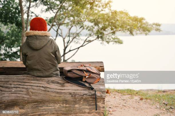Rear View Of Boy Sitting On Bench