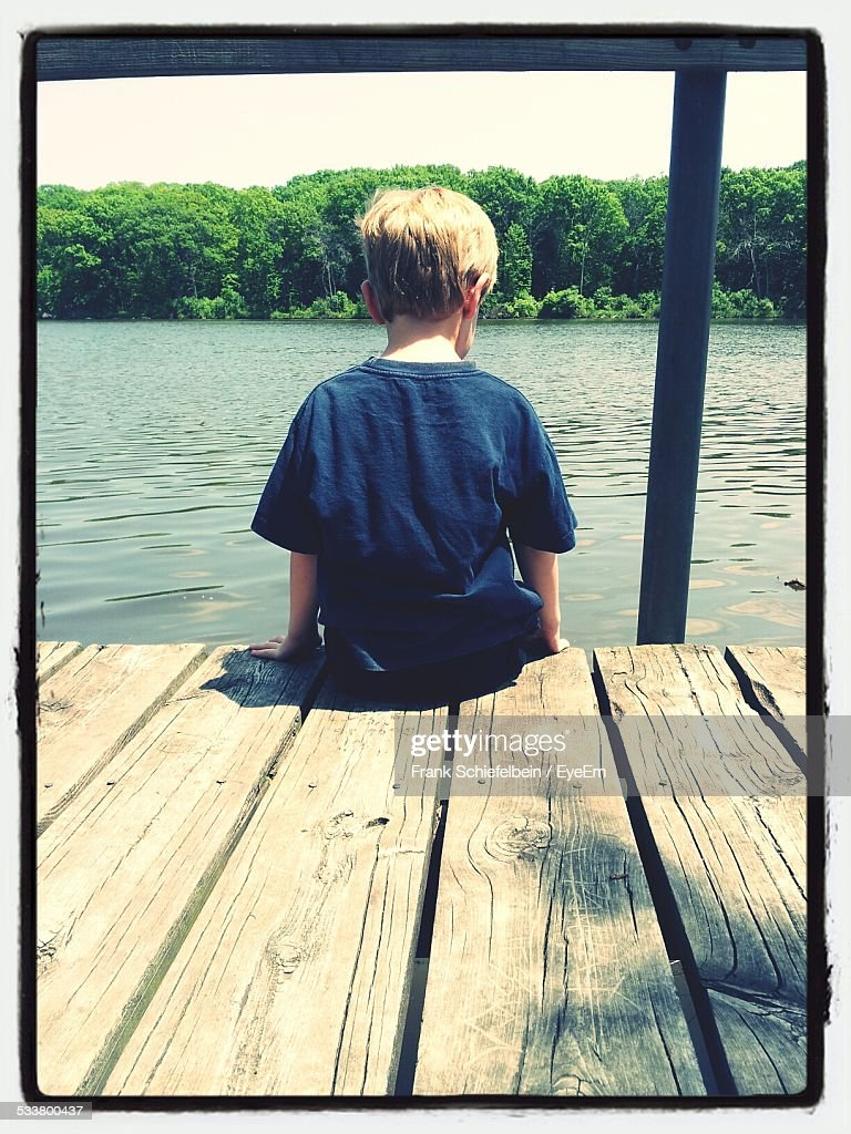 Rear View Of Boy Sitting On Jetty By Lake In Summer : Foto stock