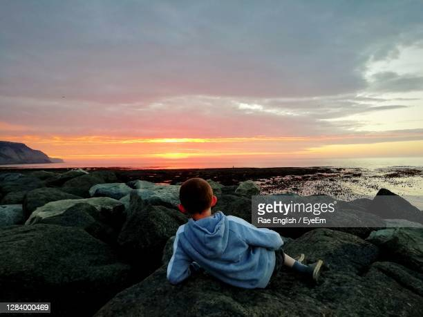 rear view of boy sitting on rock by sea against sky - one boy only stock pictures, royalty-free photos & images