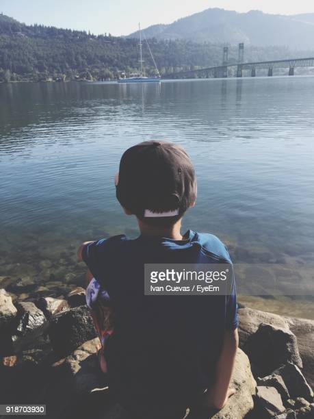 Rear View Of Boy Sitting On Rocks At Lakeshore