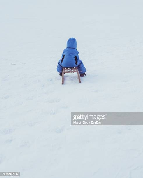 Rear View Of Boy Sitting On Sledge Over Snow Covered Field