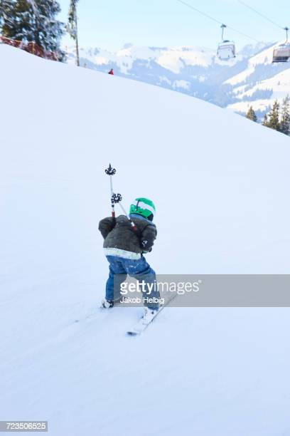 rear view of boy skiing down ski slope, gstaad, switzerland - グスタード ストックフォトと画像
