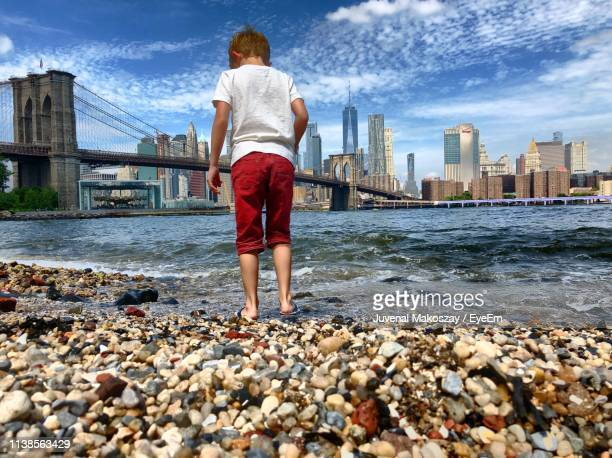 Rear View Of Boy Standing Against Brooklyn Bridge Over East River In City