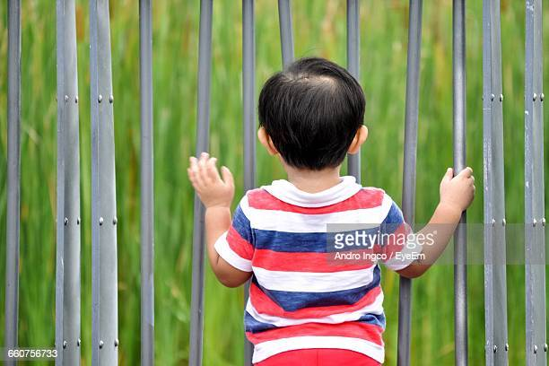 Rear View Of Boy Standing Against Fence On Field