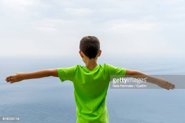 Rear View Of Boy Standing Against Sea At Beach