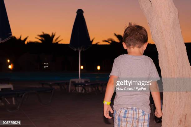 Rear View Of Boy Standing At Beach Against Sky During Sunset