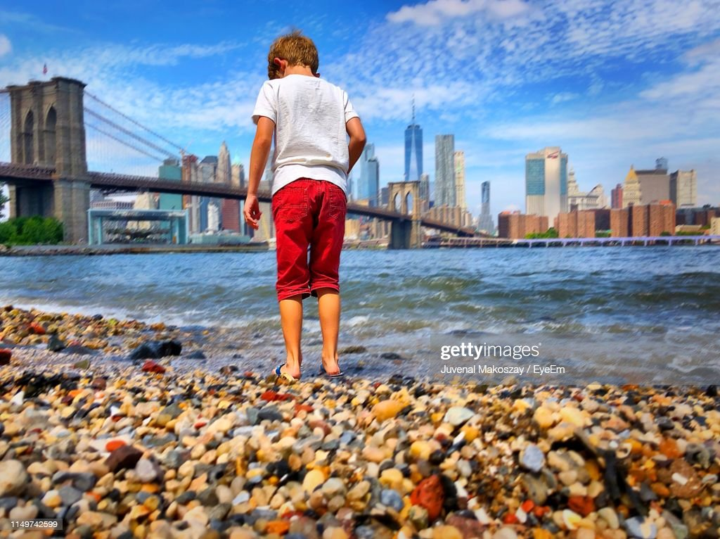 Rear View Of Boy Standing At Beach In City : Stock Photo
