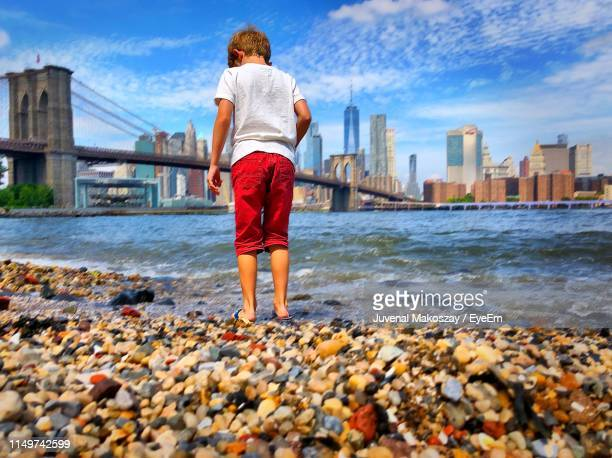 Rear View Of Boy Standing At Beach In City