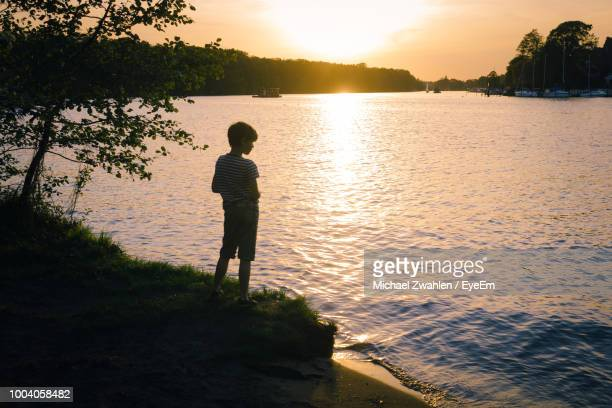 Rear View Of Boy Standing By Lake During Sunset