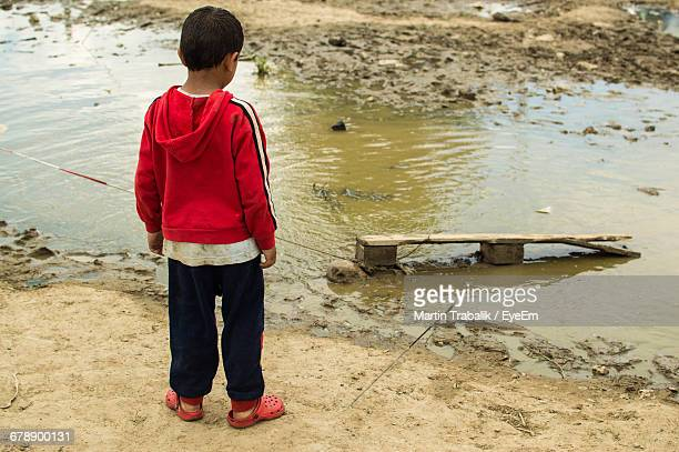 Rear View Of Boy Standing By Puddle At Refugee Camp
