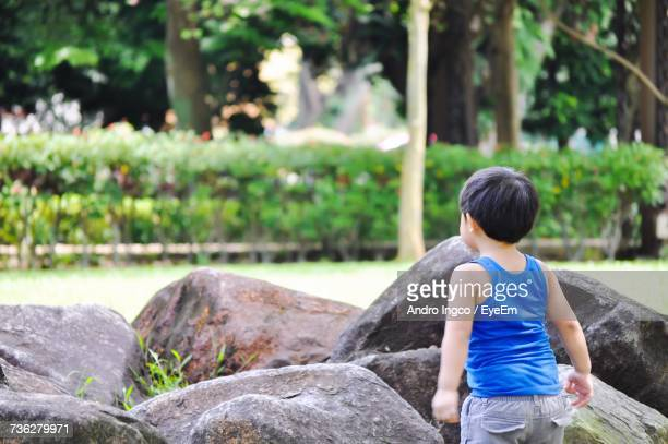 Rear View Of Boy Standing By Rocks At Public Park