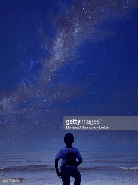 Rear View Of Boy Standing By Sea Against Sky At Night