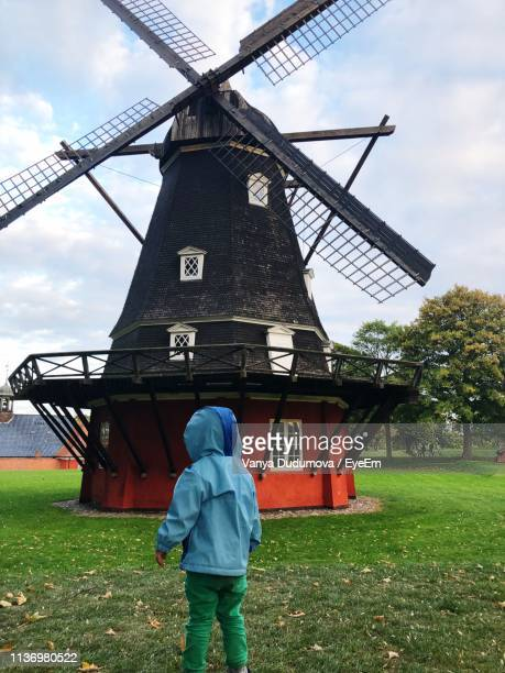 rear view of boy standing on field - traditional windmill stock photos and pictures