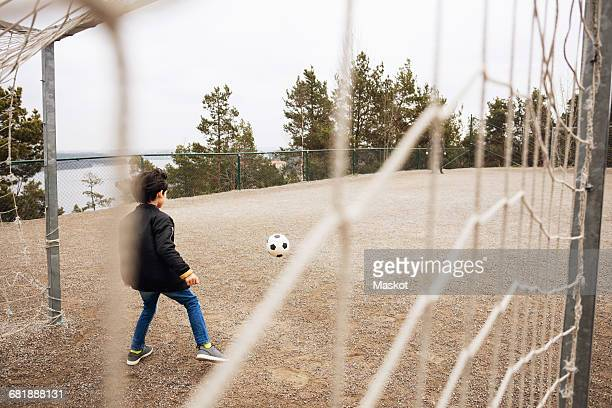 rear view of boy standing on goal post at school playground - soccer goal stock pictures, royalty-free photos & images