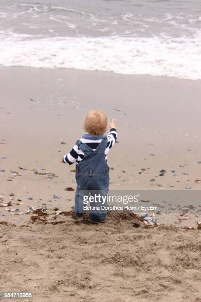 Rear View Of Boy Standing On Sand At Beach