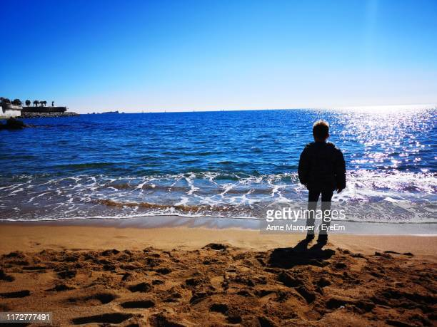 rear view of boy standing on shore at beach - marquer stock pictures, royalty-free photos & images