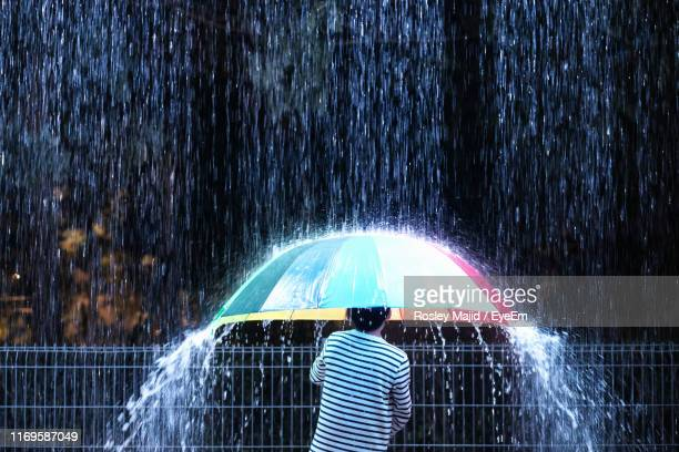 rear view of boy standing with umbrella during rainy season - torrential rain stock pictures, royalty-free photos & images