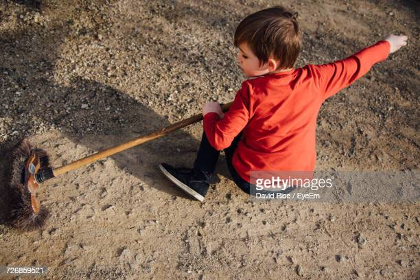 Rear View Of Boy Sweeping Field With Broom
