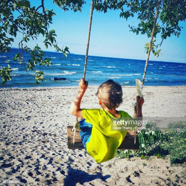 Rear View Of Boy Swinging At Beach