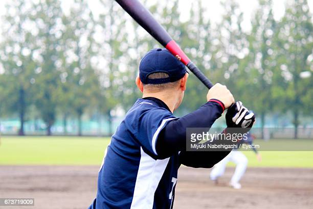 Rear View Of Boy Swinging Baseball Bat On Field
