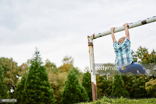 Rear view of boy swinging from goalpost