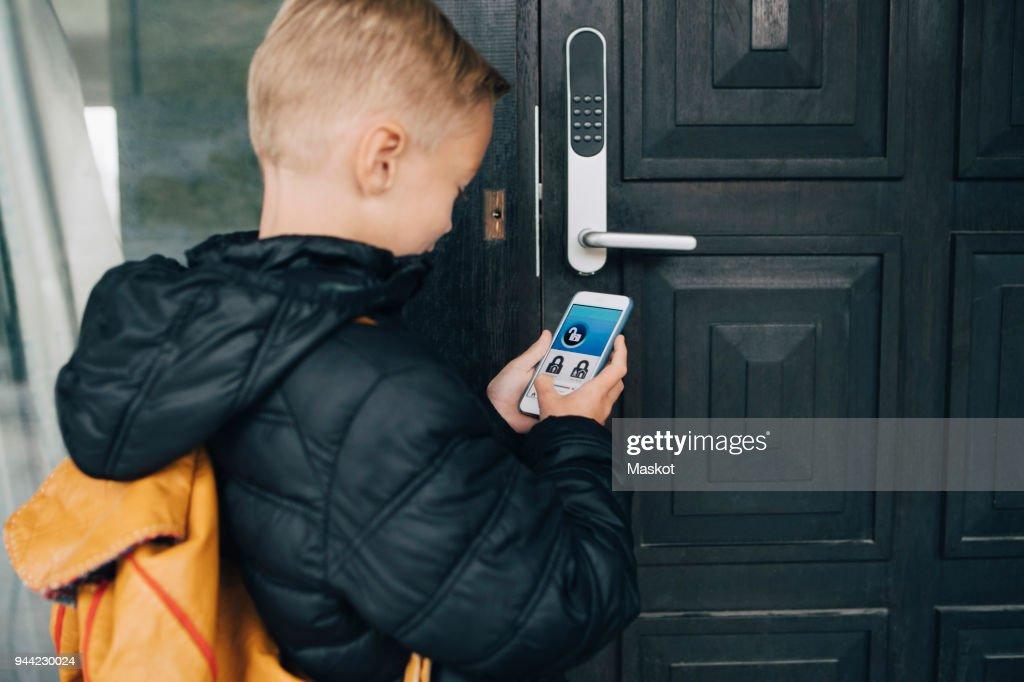 Rear view of boy using app on smart phone to unlock house door : Stock Photo