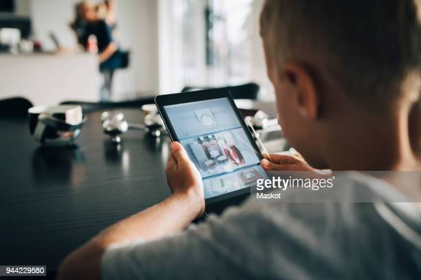 Rear view of boy using digital tablet at home