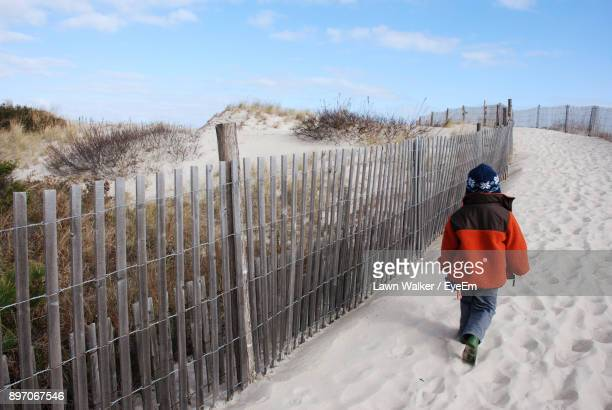 Rear View Of Boy Walking At Beach