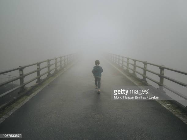 rear view of boy walking on bridge during foggy weather - chilly bin stock photos and pictures