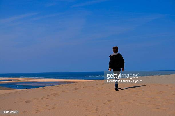 Rear View Of Boy Walking On Sand At Beach Against Sky