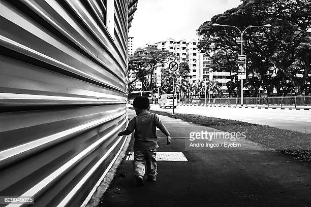 Rear View Of Boy Walking On Sidewalk By Building In City